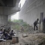 Niños pobres en India asisten a la escuela bajo un puente
