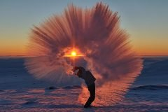 Lanzando té hirviendo frente a una puesta de sol en el círculo polar ártico