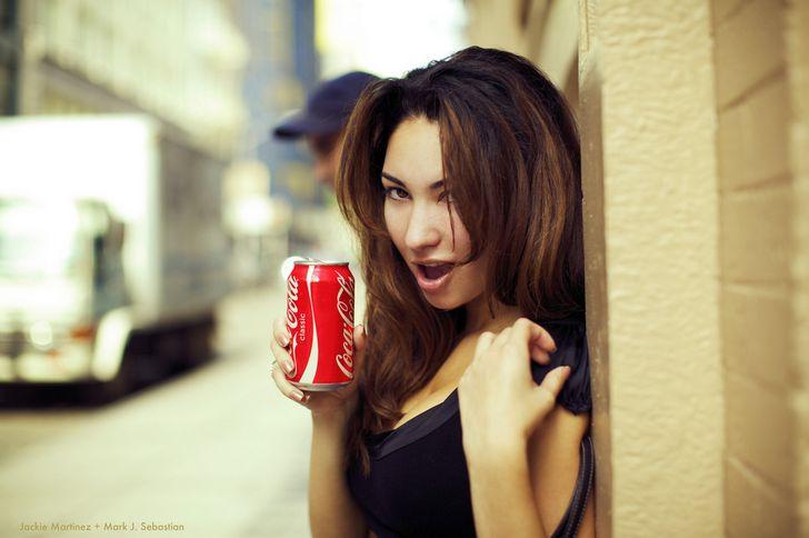 mujer sosteniendo coca cola calle