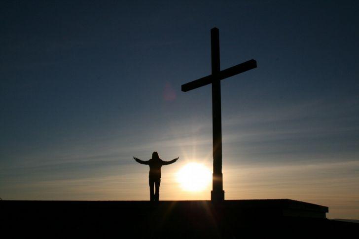 persona haciendo la cruz atardecer