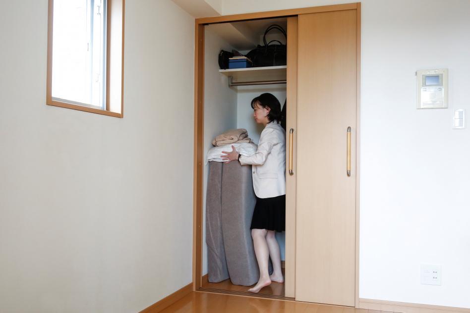 mujer guarda su ropa en armario casi vacio