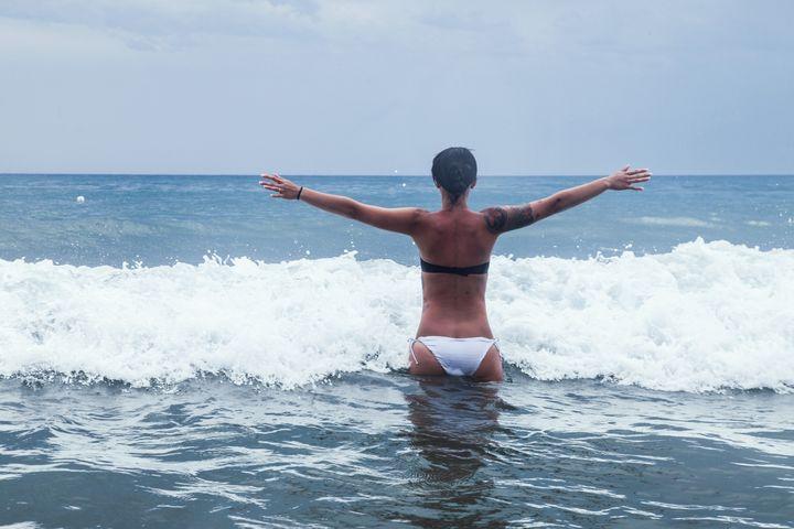 mujer brazos abiertos en las olas