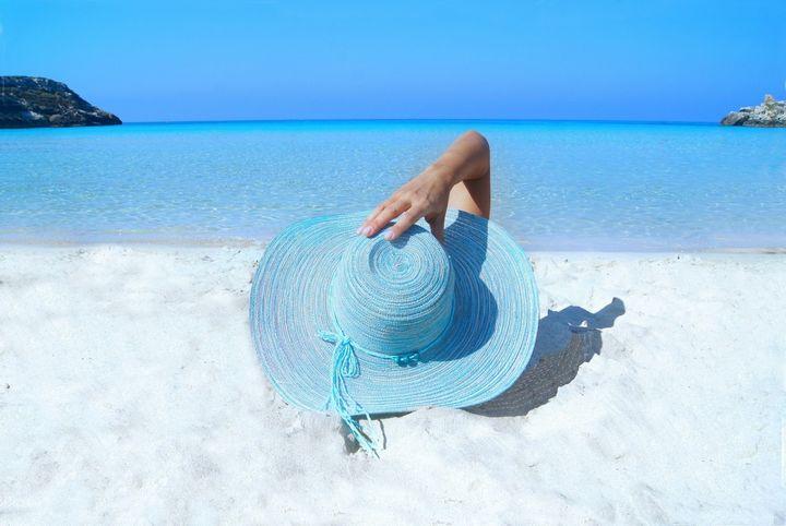 mujer sombrero descansando en la playa