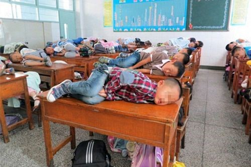 niños chinos dormidos en el salon de clases