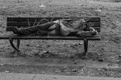 hombre alcoholizado durmiendo en una banca publica