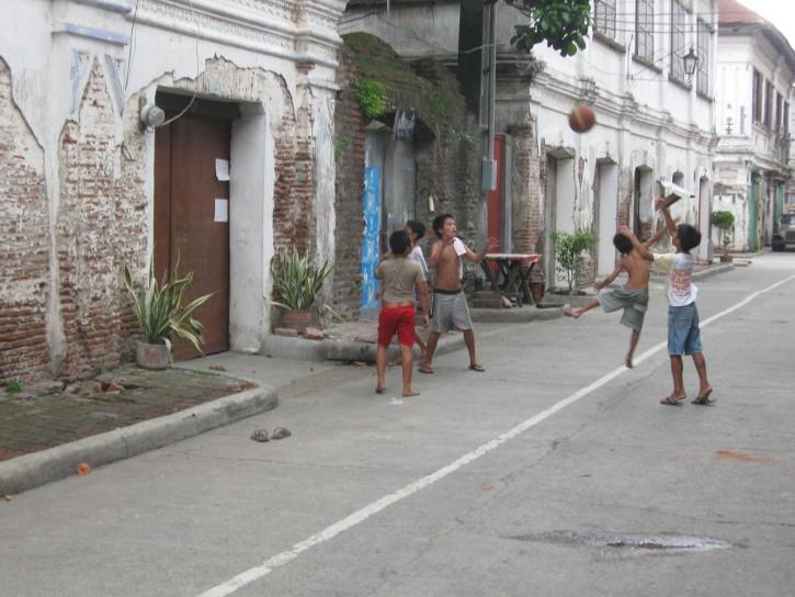 niños jugando pelota en la calle