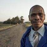 Hombre sonriendo en medio de una carretera