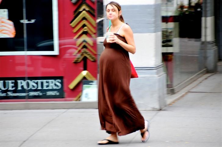 Mujer embarazada tomando cafe en la calle