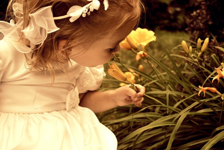 Niña oliendo flores amarillas