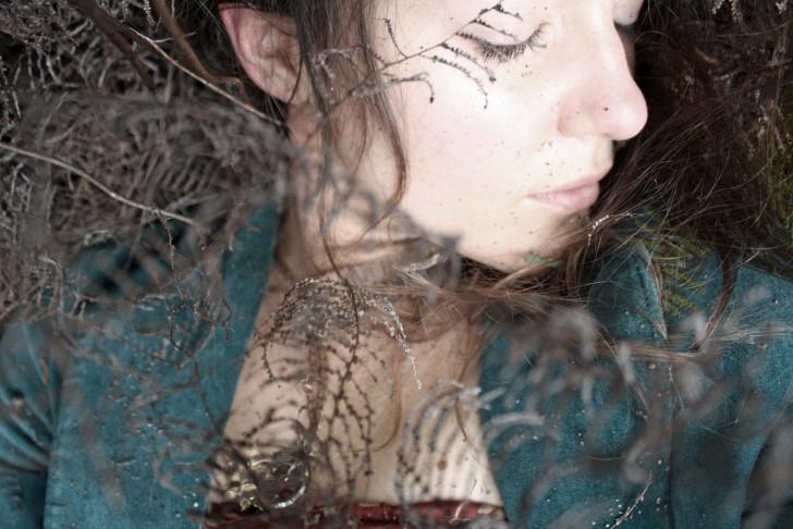 Mujer durmiendo entre ramas secas