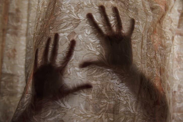 manos sobre una cortina pidiendo ayuda