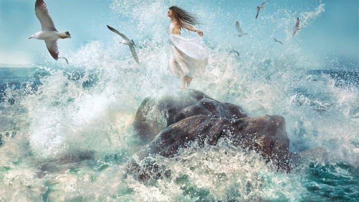 mujer sobre una roca en el oceano