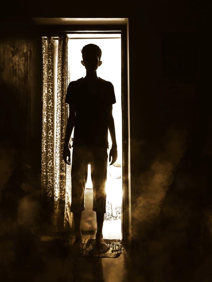 niño parado frente a una puerta silueta
