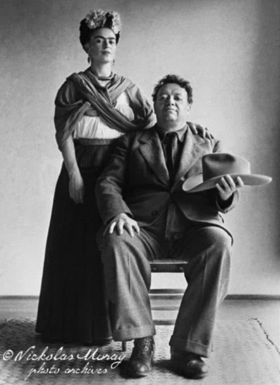 Diego senta en una silla con sombrero en mano junto a Frida