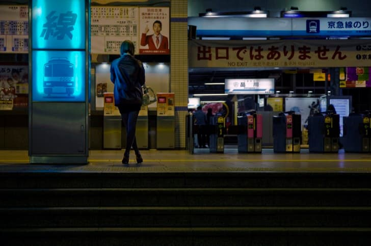 mujer solitaria esperando el metro por la noche