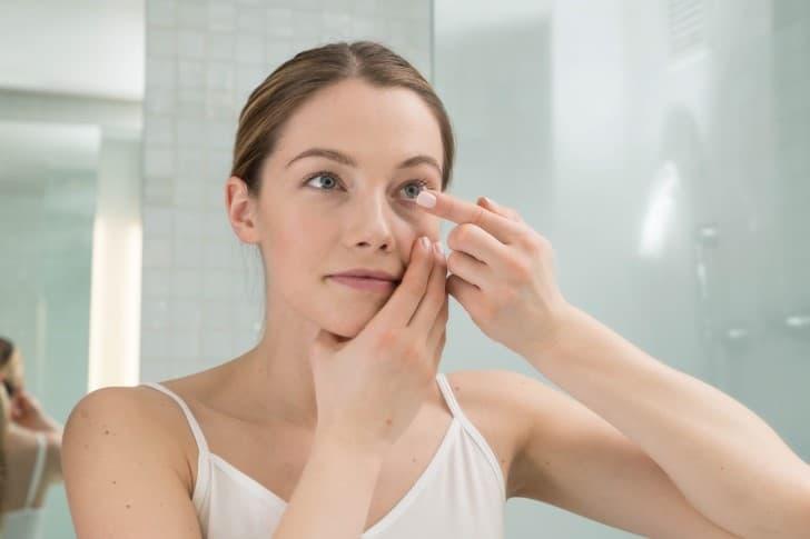 mujer colocandose lentes de contacto