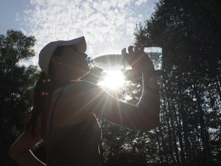 mujer hidratandose con agua embotellada