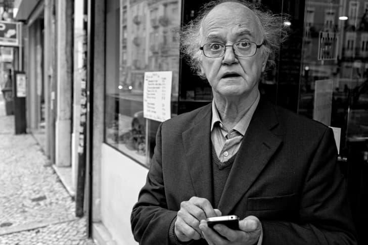 hombre anciano sorprendido leyendo telefono celular