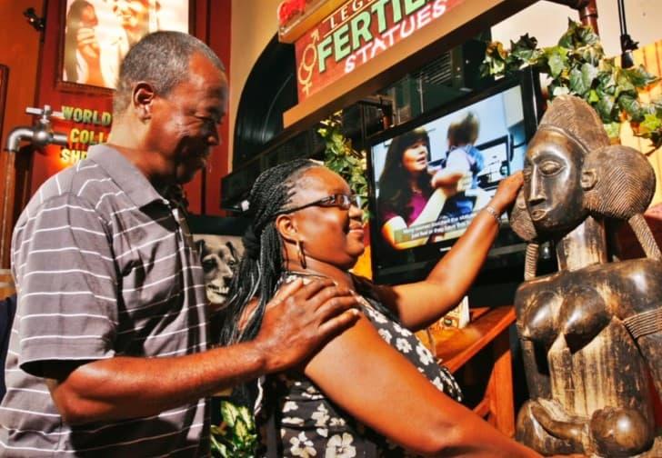mujer tocando estatuas de la fertilidad