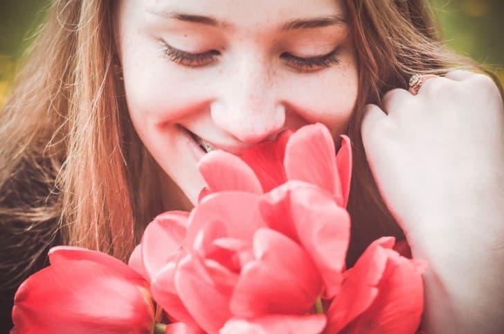 joven feliz oliendo flores