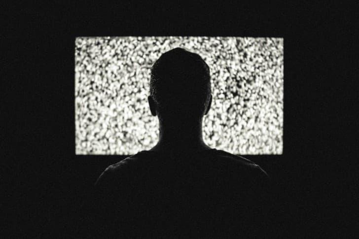 hombre observando una television con estatica