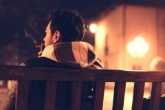 hombre sentado fumando un cigarrillo
