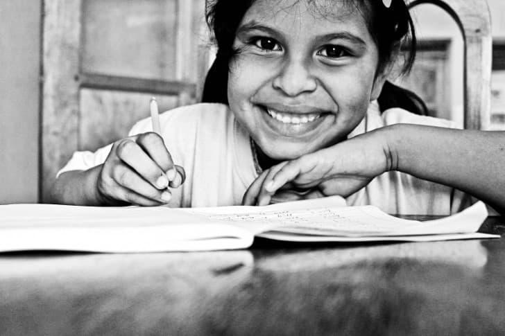 niña escribiendo con una sonrisa