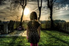 niña parada en el jardin al atardecer