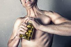 hombre abriendo un envase de pepinillos
