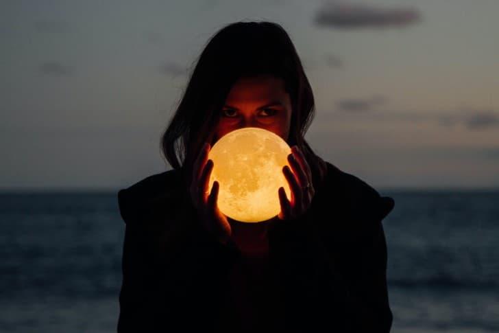 mujer sosteniendo la luna