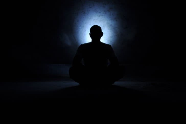 persona meditando en la oscuridad