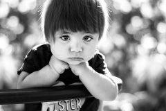 niño triste con manos en la barbilla