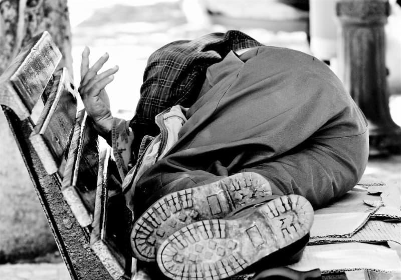 vagabundo durmiendo en una banca